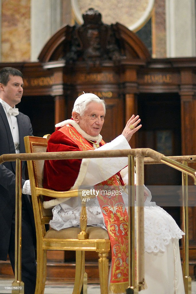 Pope Benedict XVI is pushed on a mobile trolley as he arrives during a Holy mass for the church in America on December 9, 2012 at St Peter's basilica at the Vatican. Pope Benedict XVI was holding a speech during the mass for the international congress 'Ecclesia in America'. AFP PHOTO / ALBERTO PIZZOLI