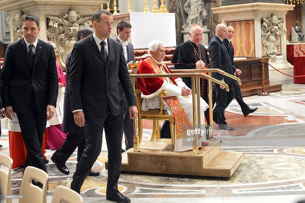 Pope Benedict XVI is pushed on a mobile trolley as he arrives during a Holy mass for the church in America on December 9, 2012 at St Peter's basilica at the Vatican. Pope Benedict XVI was holding a speech during the mass for the international congress 'Ecclesia in America'.
