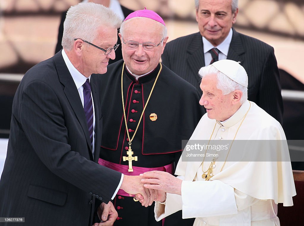<a gi-track='captionPersonalityLinkClicked' href=/galleries/search?phrase=Pope+Benedict+XVI&family=editorial&specificpeople=201771 ng-click='$event.stopPropagation()'>Pope Benedict XVI</a> (R) is welcomed by Baden Wuerttemberg state governor <a gi-track='captionPersonalityLinkClicked' href=/galleries/search?phrase=Winfried+Kretschmann&family=editorial&specificpeople=7227897 ng-click='$event.stopPropagation()'>Winfried Kretschmann</a> (L) and Freiburg's archbishop Robert Zollitsch on Muensterplatz square after visiting the Muenster cathedral on September 24, 2011 in Freiburg, Germany. The Pope is in Freiburg on the third of a four-day visit to Germany, and he will conclude his trip with an open air Sunday mass tomorrow near Freiburg.