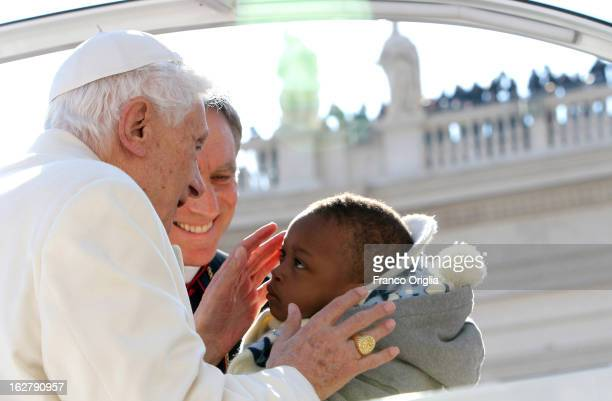 Pope Benedict XVI kisses a child as he arrives in St Peter's Square for his final general audience on February 27 2013 in Vatican City Vatican The...