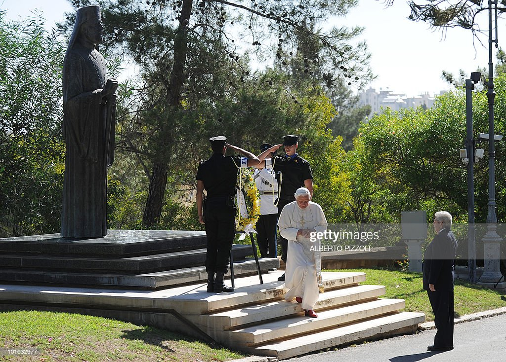 Pope Benedict XVI (C) lays a wreath at the statue of the late President of the Republic of Cyprus Archbishop Makarios III as Cypriot President Demetris Christofias (R) stands next to him (R), at the presidential palace in Nicosia on June 5, 2010 on the second day of the pontiff's visit to the mainly Greek Orthodox Mediterranean island.