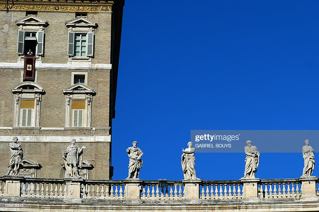 Pope Benedict XVI (top floor, L) leads the Angelus prayer from a window of his apartments on December 30, 2012 at the Vatican. AFP PHOTO / GABRIEL BOUYS