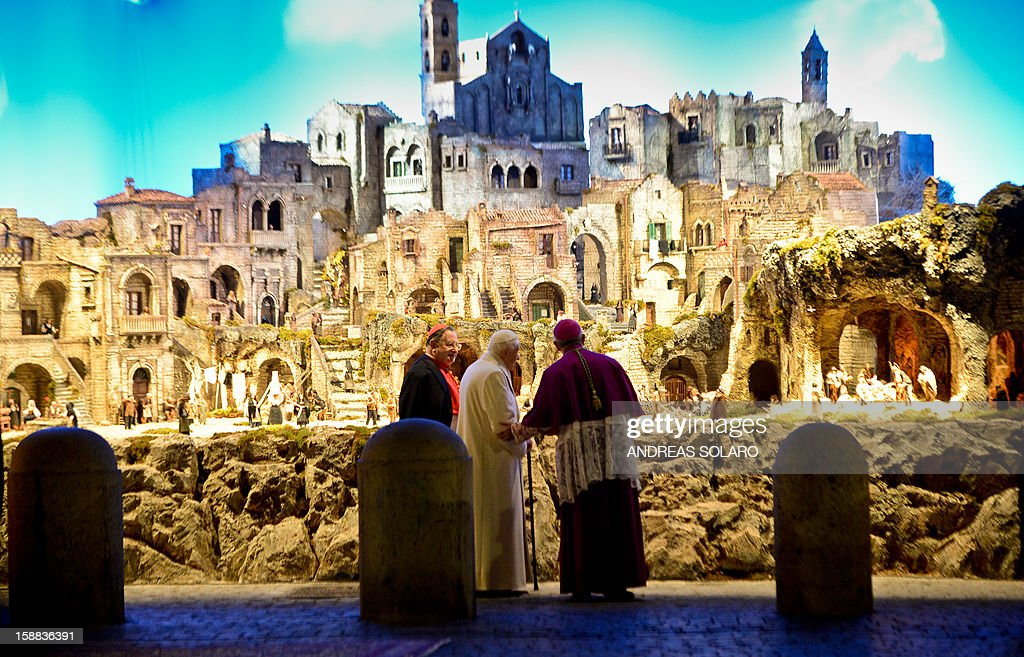 Pope Benedict XVI (C) looks at the nativity crib in Saint Peter's Square after celebrating the Vespers and Te Deum prayers in Saint Peter's Basilica at the Vatican on December 31, 2012.