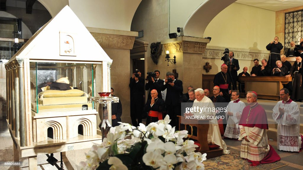 Pope Benedict XVI (C) prays at the crypt of St. Mary of Grace dedicated to Padre Pio's body (L) as the corpse of the friar lies in a coffin glass in San Giovanni Rotondo in the southern Italian Apulia region on June 21, 2009. Born Francisco Forgione, at age 23 the friar was said to have permanent sores on his hands similar to the stigmata, or the wounds of Jesus Christ's crucifixion, according to Christian belief. Padre Pio has become a cult figure for millions around the world and the subject of controversy in Italy. AFP PHOTO/ Andreas SOLARO