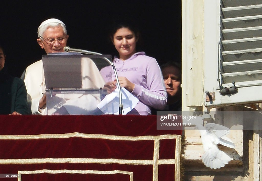 Pope Benedict XVI releases a dove from the window of his appartment at the end of his Sunday Angelus prayer in St. Peter's square at the Vatican on January 27, 2013. The Pontiff and youth of the Catholic Action released two doves, symbol of peace. AFP PHOTO / VINCENZO PINTO
