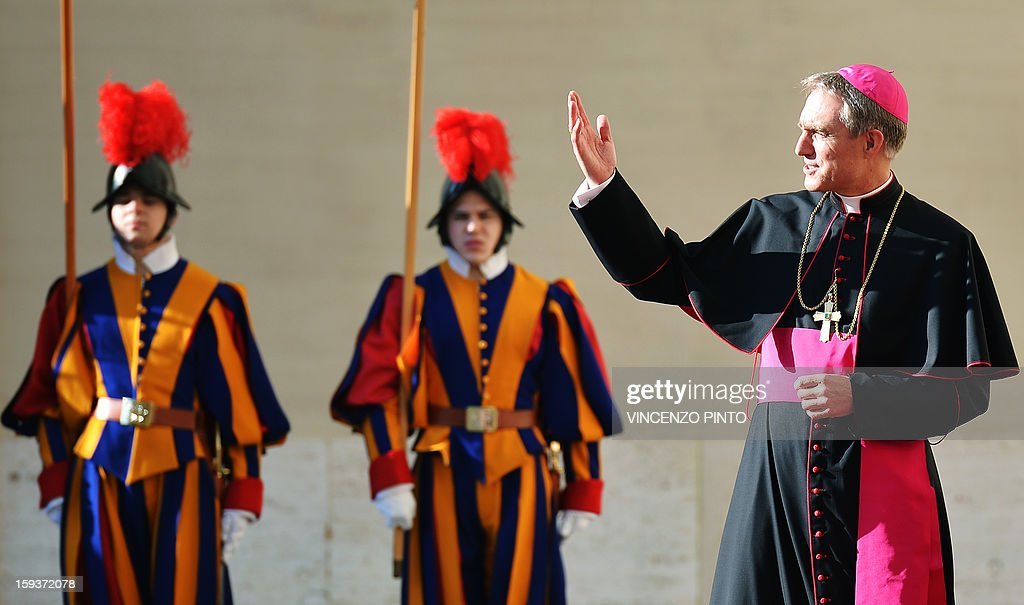 Pope Benedict XVI 's personal secretary Georg Gaenswein (R ) gestures as he wait for Prince Albert II of Monaco and his wife Princess Charlene ahead of a private audience with the pontiff at the Vatican on January 12, 2013.