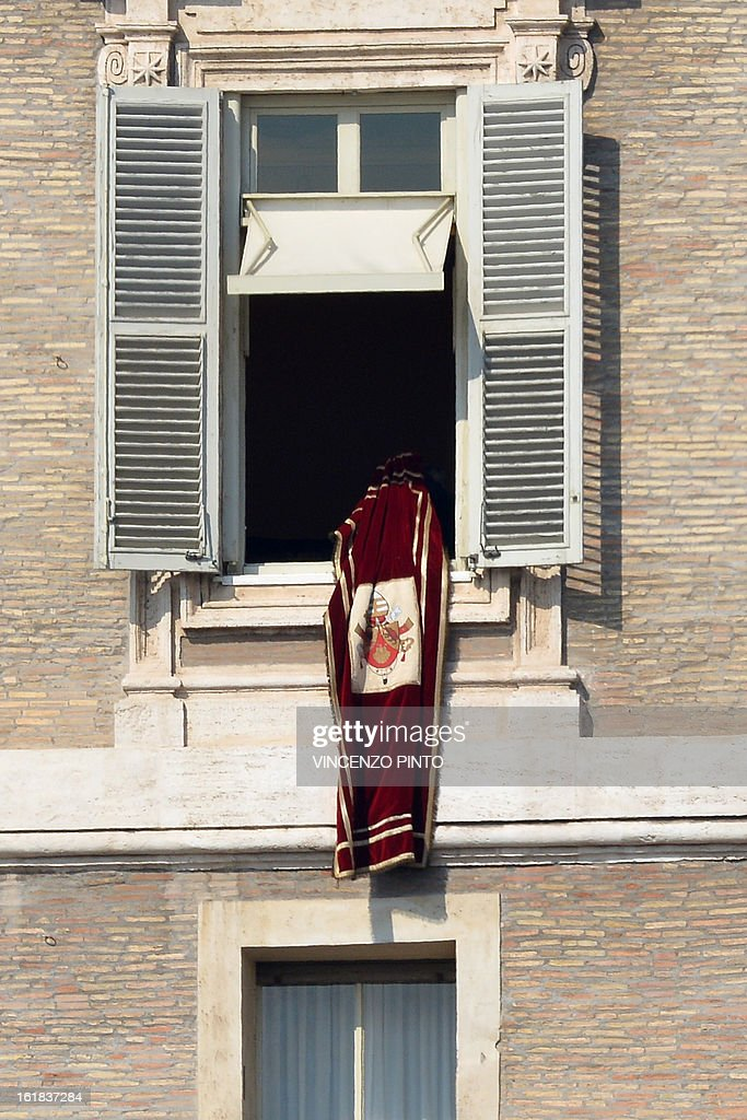 Pope Benedict XVI's secretary and prefect of the Papal household Georg Gaenswein takes off the Vatican's flag after the Pontiff's lead the Angelus prayer from the window of his appartmnents on February 17, 2013 at the Vatican. The Vatican the day before said it could speed up the election of a new pope as lobbying for Benedict XVI's job intensified amid speculation over who had the best chance to succeed him. AFP PHOTO / VINCENZO PINTO