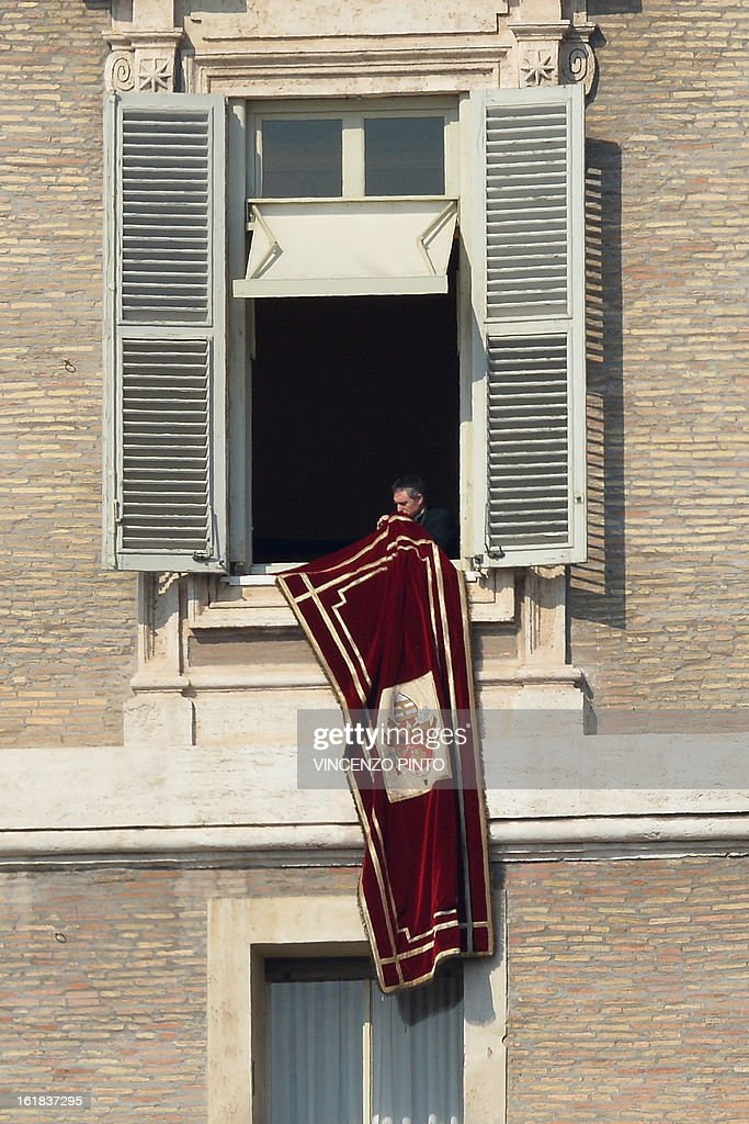 Pope Benedict XVI's secretary and prefect of the Papal household Georg Gaenswein takes off the Vatican's flag after the Pontiff's lead the Angelus prayer from the window of his appartmnents on February 17, 2013 at the Vatican. The Vatican the day before said it could speed up the election of a new pope as lobbying for Benedict XVI's job intensified amid speculation over who had the best chance to succeed him.
