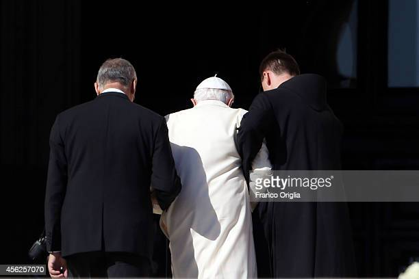 Pope Emeritus Benedict XVI is helped as he leaves St Peter's Square after a celebration for grandparents and the elderly held by Pope Francis on...