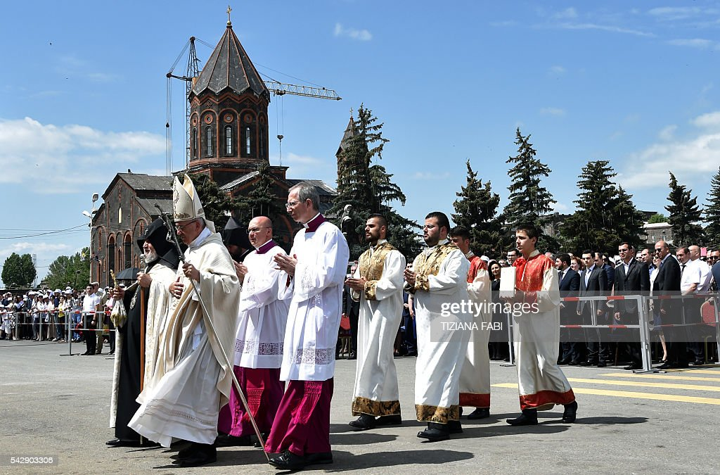 Pope Francis (2nd L), accompanied by Catholicos of All Armenians Karekin II (L), arrives to lead an open-air mass in Vartanants Square in Armenia's second-largest city of Gyumri on June 25, 2016. / AFP / TIZIANA