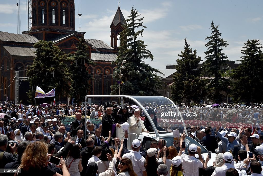Pope Francis, accompanied by Catholicos of All Armenians Karekin II, waves to the crowd from the popemobile after an open-air mass in Armenia's second-largest city of Gyumri on June 25, 2016. / AFP / TIZIANA