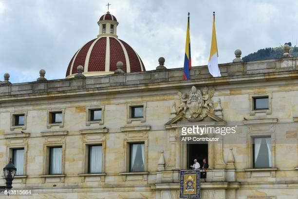 Pope Francis accompanied by the Archbishop of Bogota Cardinal Jesus Ruben Salazar delivers a speech from a balcony of the Archbishop's Palace to...