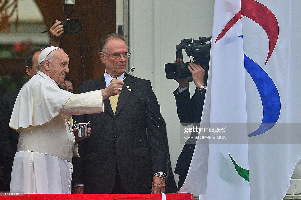 Pope Francis, accompanied by the president of the Brazilian Olympic Committee, Carlos Arthur Nuzman (R), blesses the Rio 2016 Olympic flag ahead of the 2016 Summer Games, at the City Palace in Rio de Janeiro where he will also receive the keys of the city, on July 25, 2013. The first Latin American and Jesuit pontiff arrived in Brazil mainly for the huge five-day Catholic gathering World Youth Day.