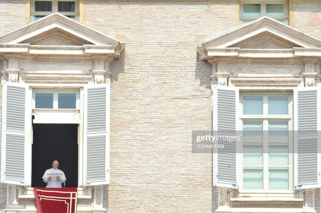 Pope Francis addresses the crowd from the window of the apostolic palace overlooking St.Peter's square during his Sunday Angelus prayer on August 25, 2013 at the Vatican.