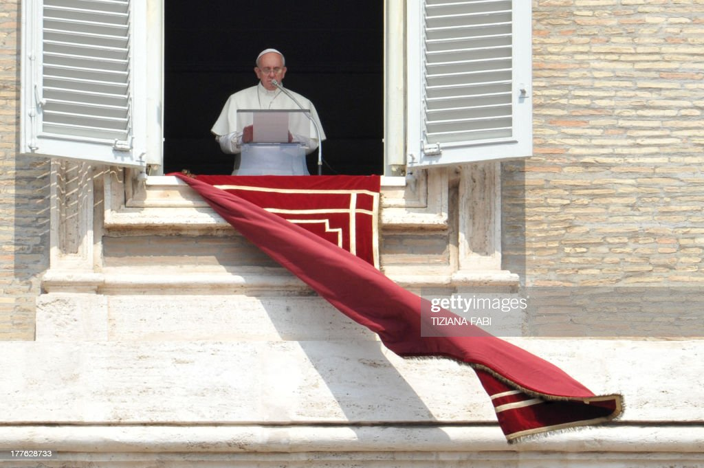 Pope Francis addresses the crowd from the window of the apostolic palace overlooking St.Peter's square during his Sunday Angelus prayer on August 25, 2013 at the Vatican. AFP PHOTO / TIZIANA FABI