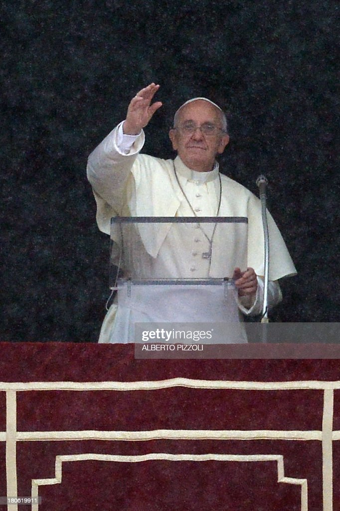 Pope Francis addresses the crowd from the window of the apostolic palace overlooking St.Peter's square, as it rains, during his Sunday Angelus prayer on September 15, 2013.