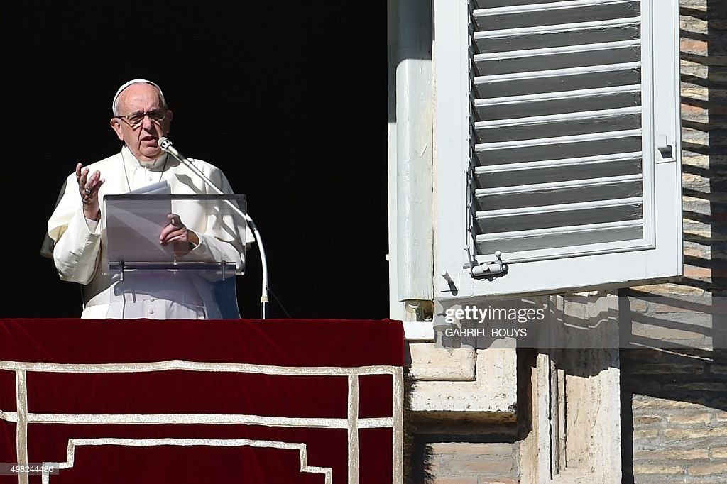 Pope Francis addresses the crowd from the window of the apostolic palace overlooking St.Peter's square during his Sunday Angelus prayer on November 22, 2015 at the Vatican. AFP PHOTO / GABRIEL BOUYS