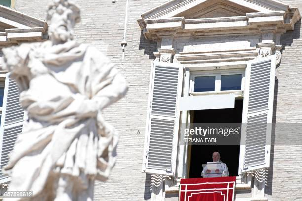 Pope Francis addresses the crowd from the window of the apostolic palace overlooking St Peter's square during the Sunday Angelus prayer on March 26...