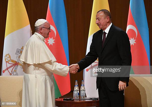 Pope Francis and Azerbaijan's President Ilham Aliyev shake hands at the Aliyev congress center during a meeting with the authorities in Baku...