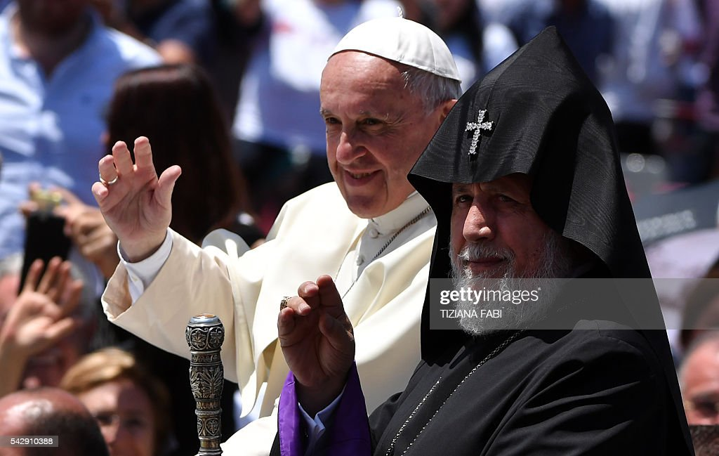 Pope Francis and Catholicos of All Armenians Karekin II wave to the crowd from the popemobile after an open-air mass in Armenia's second-largest city of Gyumri on June 25, 2016. / AFP / TIZIANA