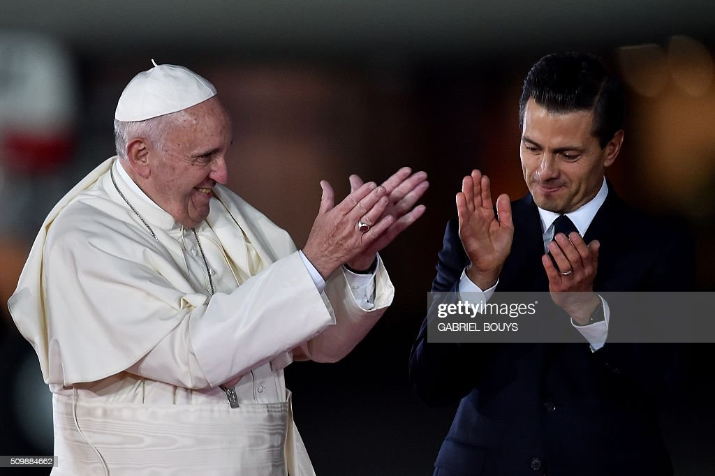 Pope Francis (L) and Mexican President Enrique Pena Nieto (R) applaud a performance at Benito Juarez international airport in Mexico City on February 12, 2016. Catholic faithful flocked to the streets of Mexico City to greet Pope Francis on Friday after the pontiff held a historic meeting with the head of the Russian Orthodox Church in Cuba. AFP PHOTO/ GABRIEL BOUYS / AFP / GABRIEL BOUYS