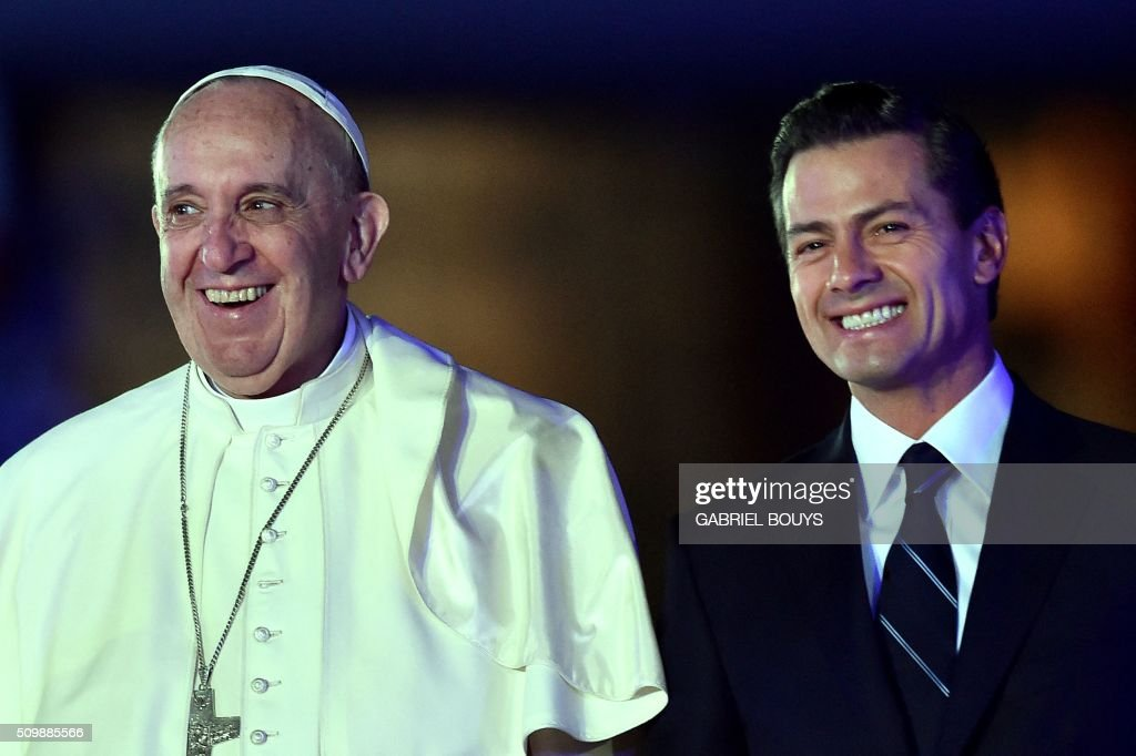 Pope Francis (L) and Mexican President Enrique Pena Nieto (R) smile upon the Pope's arrival at Benito Juarez international airport in Mexico City on February 12, 2016. Catholic faithful flocked to the streets of Mexico City to greet Pope Francis on Friday after the pontiff held a historic meeting with the head of the Russian Orthodox Church in Cuba. AFP PHOTO/ GABRIEL BOUYS / AFP / GABRIEL BOUYS