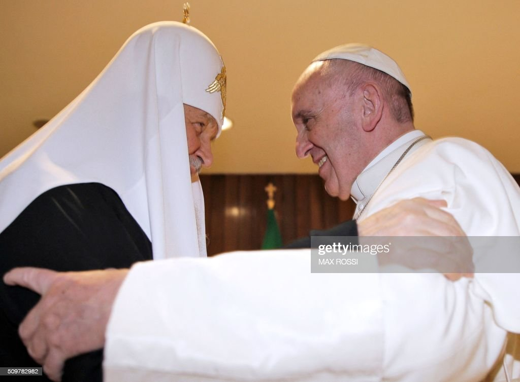 Pope Francis (R) and the head of the Russian Orthodox Church, Patriarch Kirill, greet each other during a historic meeting in Havana on February 12, 2016. Pope Francis and Russian Orthodox Patriarch Kirill kissed each other and sat down together Friday for the first meeting between their two branches of the church in nearly a thousand years. Francis, 79, in white robes and a skullcap and Kirill, 69, in black robes and a white headdress, exchanged kisses and embraced before sitting down smiling for the historic meeting at Havana airport. AFP PHOTO / MAX ROSSI / POOL / AFP / POOL / Max ROSSI