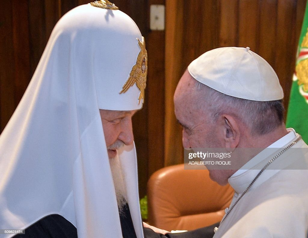Pope Francis (R) and the head of the Russian Orthodox Church, Patriarch Kirill, greet each other during a historic meeting in Havana on February 12, 2016. Pope Francis and Russian Orthodox Patriarch Kirill kissed each other and sat down together Friday for the first meeting between their two branches of the church in nearly a thousand years. Francis, 79, in white robes and a skullcap and Kirill, 69, in black robes and a white headdress, exchanged kisses and embraced before sitting down smiling for the historic meeting at Havana airport. AFP PHOTO / ADALBERTO ROQUE / AFP / POOL / ADALBERTO ROQUE