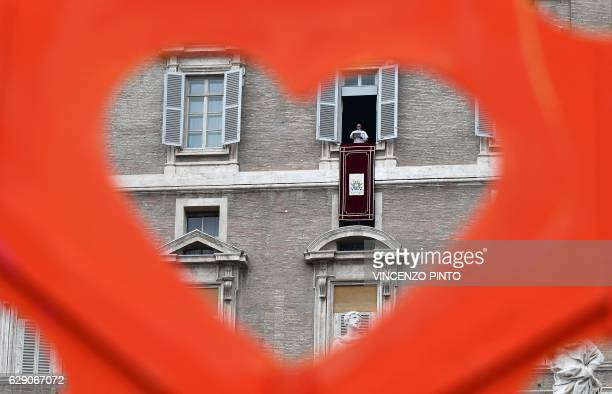 Pope Francis appears through a heartshaped banner during the traditional blessing of figurines as part of his Sunday Angelus prayer before Christmas...