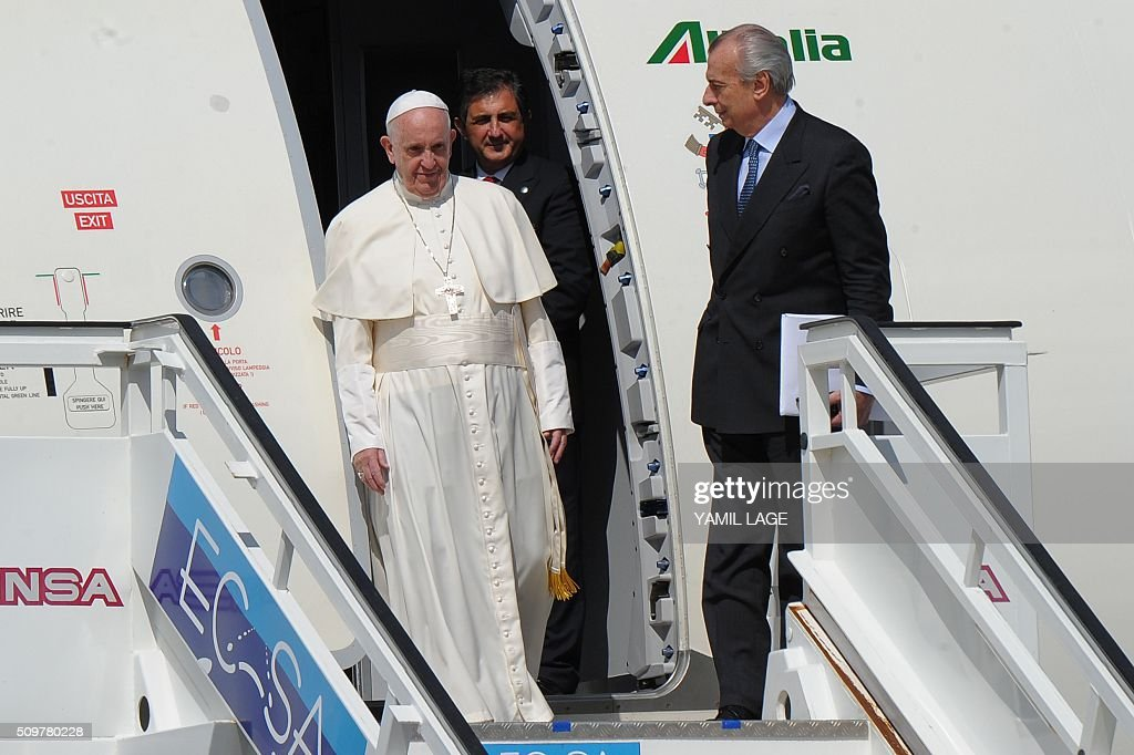 Pope Francis arrives at the International Airport Jose Marti in Havana, on February 12, 2016. Pope Francis landed in Cuba Friday to meet with the head of the Russian Orthodox Church, the first such encounter since the two branches of Christianity split a millennium ago. The 79-year-old pontiff, in his white robes, stepped off an Alitalia plane and shook hands with Cuban President Raul Castro on the tarmac at Jose Marti airport, where he was then due to sit down with the Russian Patriarch Kirill. AFP PHOTO / YAMIL LAGE / AFP / YAMIL LAGE