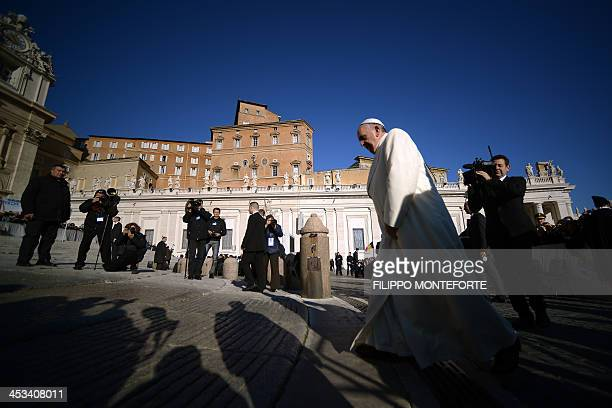 Pope Francis arrives for his general audience in St Peter's square at the Vatican on December 4 2013 AFP PHOTO / FILIPPO MONTEFORTE