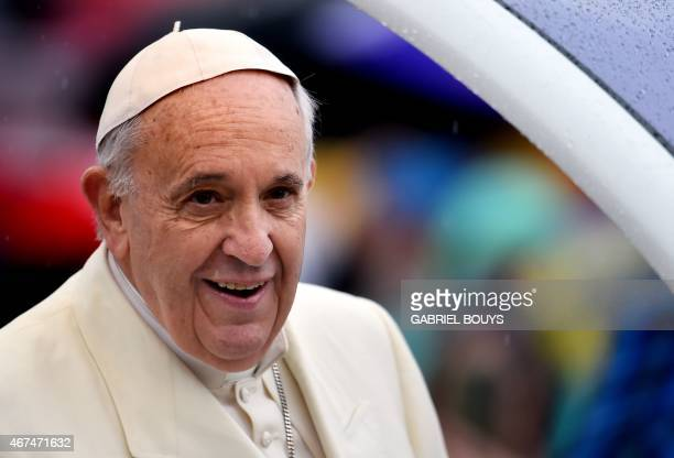 Pope Francis arrives under heavy rain for his weekly general audience in St Peter's square at the Vatican on March 25 2015 AFP PHOTO / GABRIEL BOUYS