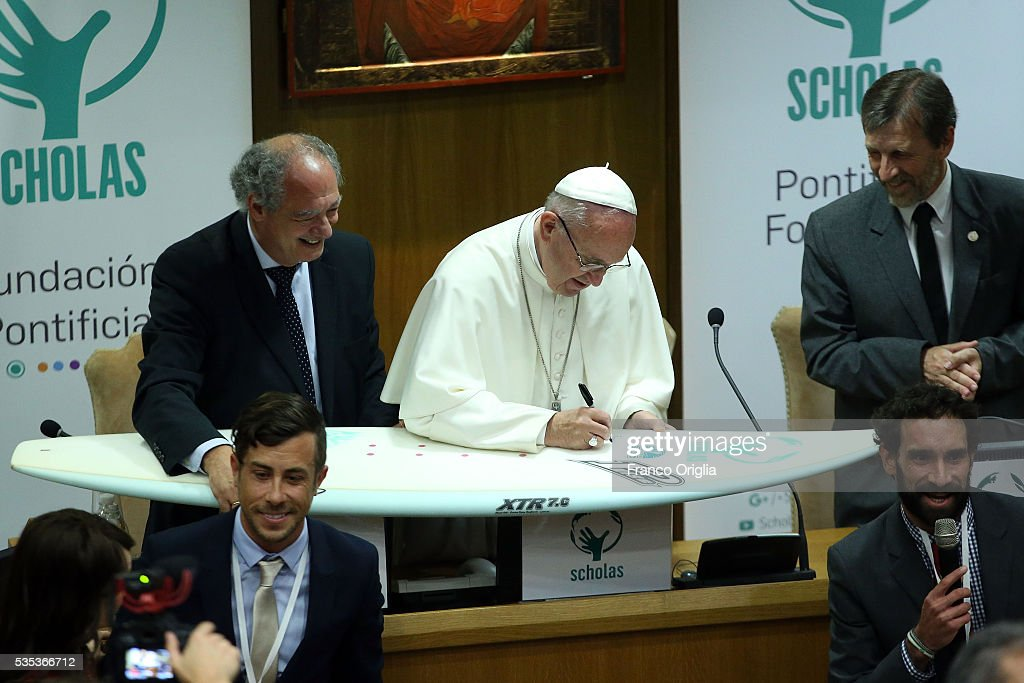 Pope Francis autographs a surf board during 'Un Muro o Un Ponte' Seminary held by Pope Francis at the Paul VI Hall on May 29, 2016 in Vatican City, Vatican.