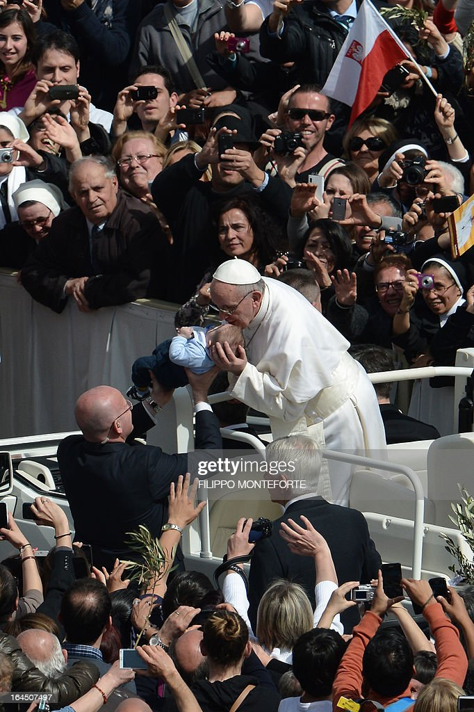 Pope Francis blesses a baby after a mass on St Peter's square as part of the Palm Sunday celebration on March 24, 2013 at the Vatican. The Palm Sunday marks the start of the holy week of Easter in celebration of the crucifixion and resurrection of Jesus Christ. AFP PHOTO / FILIPPO MONTEFORTE