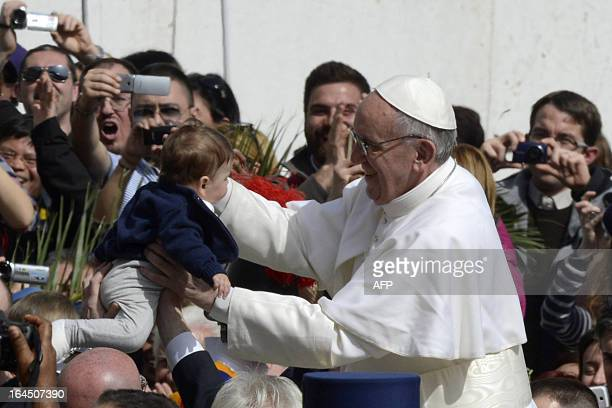 Pope Francis blesses a baby as he leaves at the end of a mass at St Peter's square as part of the Palm Sunday celebration on March 24 2013 at the...
