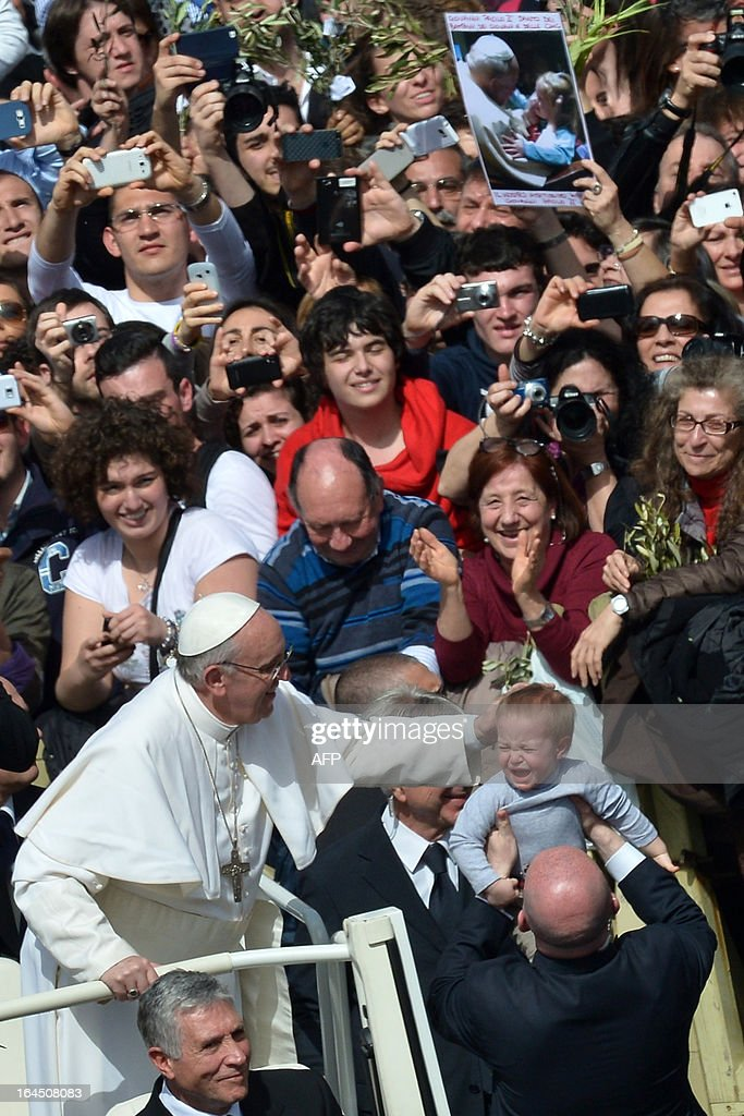 Pope Francis blesses a baby as he leaves at the end of a mass at St Peter's square as part of the Palm Sunday celebration on March 24, 2013 at the Vatican. The Palm Sunday marks the start of the holy week of Easter in celebration of the crucifixion and resurrection of Jesus Christ. AFP PHOTO / GABRIEL BOUYS