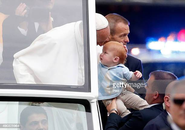 Pope Francis blesses a baby in the Popemobile during a parade September 27 2015 in Philadelphia Pennsylvania Pope Francis is in Philadelphia for the...