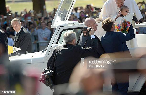 Pope Francis blesses a child handed to him during a parade on the streets around the Ellipse south of the White House September 23 2015 in Washington...