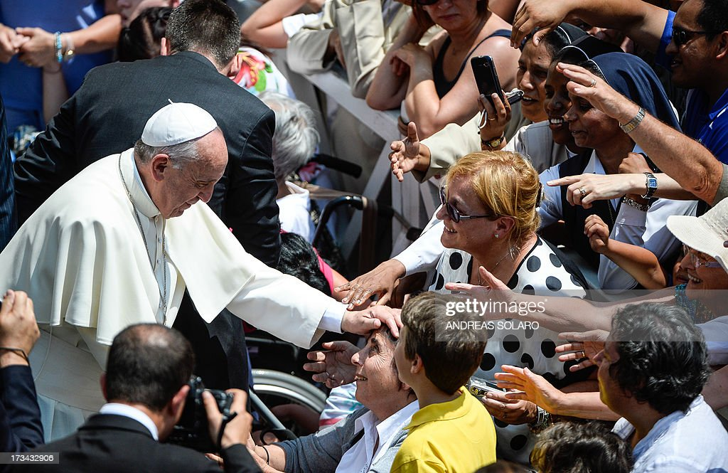 Pope Francis (L) blesses people gathered on July 14, 2013, at the end of his first Angelus prayer in front of his summer residence in Castel Gandolfo, 40 kms southeast of Rome. AFP PHOTO / ANDREAS SOLARO