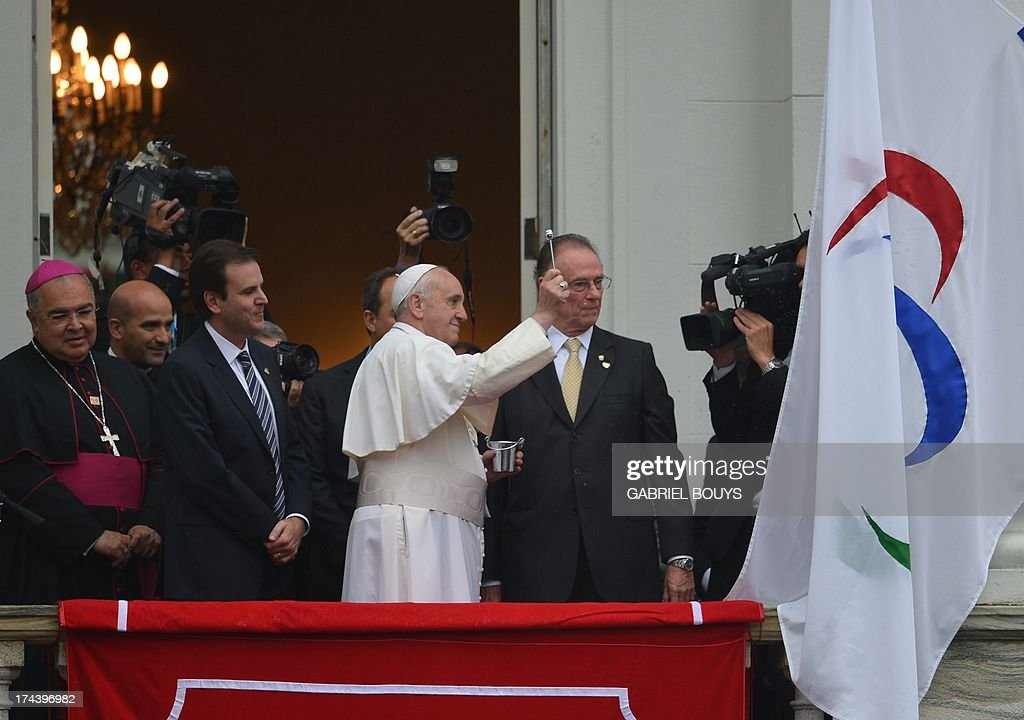 Pope Francis (C) blesses the Rio 2016 Olympic flag ahead of the 2016 Summer Games, at the City Palace in Rio de Janeiro where he will also receive the keys of the city, on July 25, 2013. The first Latin American and Jesuit pontiff arrived in Brazil mainly for the huge five-day Catholic gathering World Youth Day.