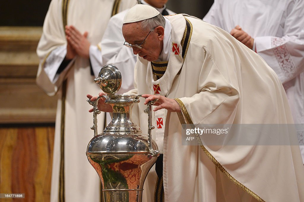 Pope Francis blows inside an amphora containing holy oil as he leads the Chrism mass on holy Thursday on March 28, 2013 at the St Peter basilica at the Vatican.