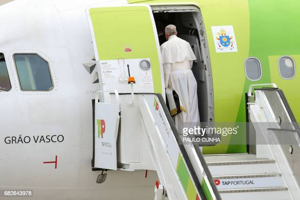 Pope Francis boards in an airplane upon his departure from Portugal on its way to Rome at Monte Real air base in Leiria on May 13 2017 The two young...