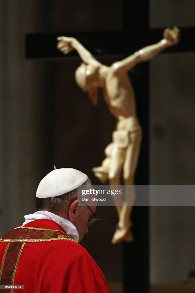 Pope Francis bows his head in front of a crucifix as he presides over a Papal Mass with the Celebration of the Lord's Passion inside St Peter's Basilica on March 29, 2013 in Vatican City, Vatican. Pope Francis is taking part in his first holy week as pontiff and will later today preside over the Way Of the Cross procession at the Colosseum in Rome.