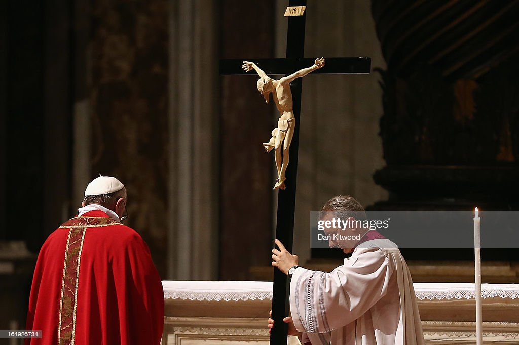 Pope Francis bows his head in front of a crucifix during a Papal Mass with the Celebration of the Lord's Passion inside St Peter's Basilica on March 29, 2013 in Vatican City, Vatican. Pope Francis is taking part in his first holy week as pontiff and will later today preside over the Way Of the Cross procession at the Colosseum in Rome.