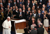 Pope Francis bows while being applauded by members of Congress as he arrives to speak during a joint meeting of the US Congress in the House Chamber...