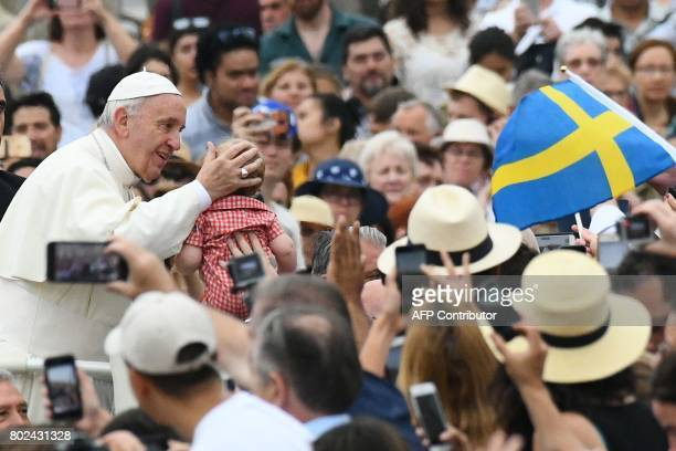 Pope Francis caresses the head of a baby as he arrives for a weekly general audience at St Peter's square on June 28 2017 in Vatican / AFP PHOTO /...