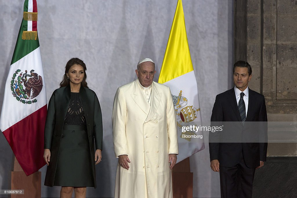 Pope Francis, center, Enrique Pena Nieto, Mexico's president, right, and Pena Nieto's wife, Angelica Rivera, left, stand during the welcoming ceremony at The National Palace in Mexico City, Mexico on Saturday, Feb. 13, 2016. Pope Francis is scheduled to celebrate mass at the Basilica of Guadalupe on Saturday night during his trip to Mexico which runs through Wednesday. Photographer: Susana Gonzalez/Bloomberg via Getty Images