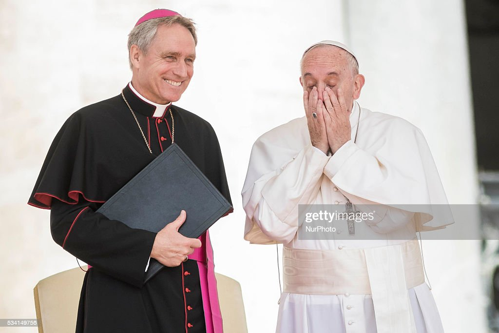 Pope Francis covers his faces as he laughs with Archbishop Georg Gaenswein during his Weekly General Audience in St. Peter's Square in Vatican City, Vatican on May 25, 2016. At the conclusion of his weekly General Audience, Pope Francis prayed for the victims of terrorist attacks that took place in Syria on Monday.