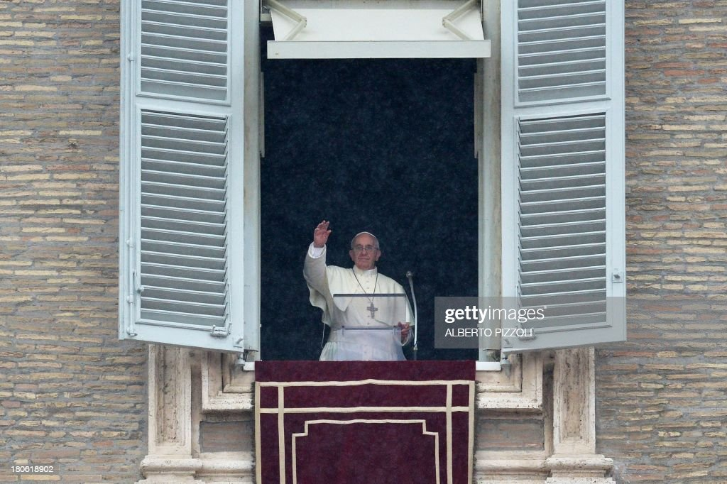 Pope Francis delivers a speech from the window of his appartment as it rains during his Sunday Angelus prayer in St Peter's square at the Vatican on September 15, 2013.