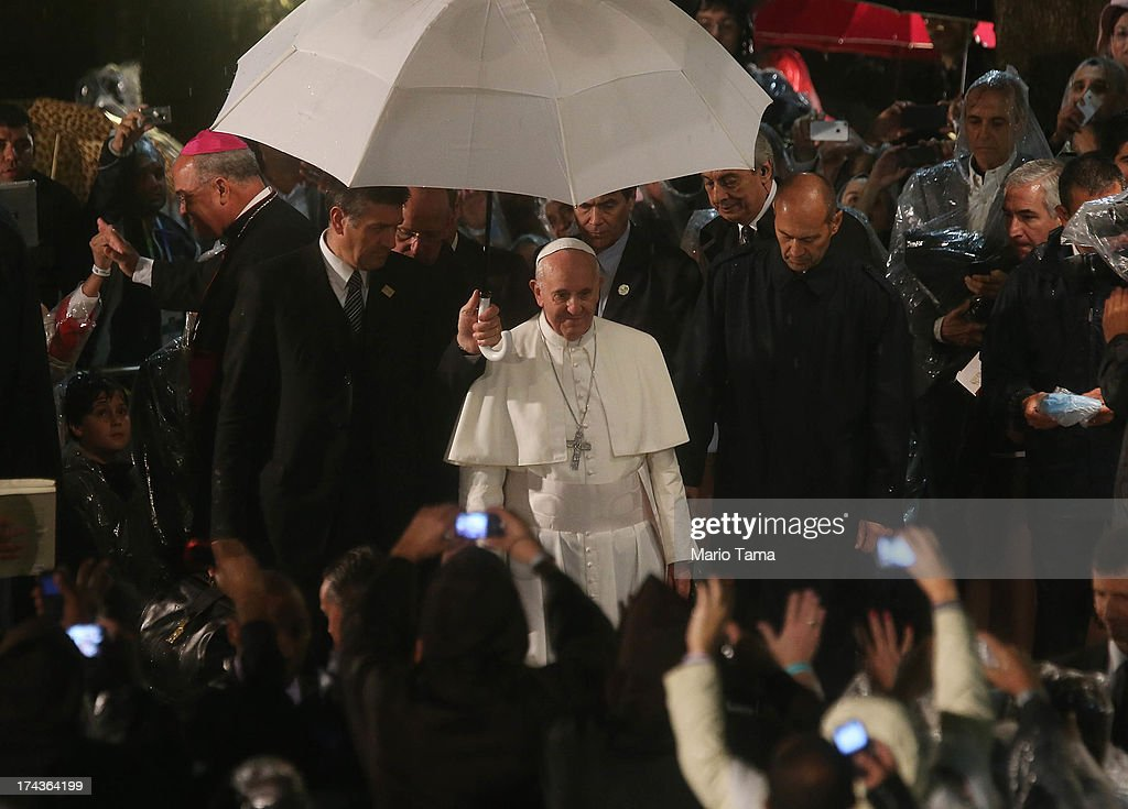 <a gi-track='captionPersonalityLinkClicked' href=/galleries/search?phrase=Pope+Francis&family=editorial&specificpeople=2499404 ng-click='$event.stopPropagation()'>Pope Francis</a> (C) departs in the rain after speaking at the Hospital de Sao Francisco de Assis (Hospital of Saint Francis of Assisi) on July 24, 2013 in Rio de Janeiro, Brazil. More than 1.5 million pilgrims are expected to join <a gi-track='captionPersonalityLinkClicked' href=/galleries/search?phrase=Pope+Francis&family=editorial&specificpeople=2499404 ng-click='$event.stopPropagation()'>Pope Francis</a> for his visit to the Catholic Church's World Youth Day celebrations. <a gi-track='captionPersonalityLinkClicked' href=/galleries/search?phrase=Pope+Francis&family=editorial&specificpeople=2499404 ng-click='$event.stopPropagation()'>Pope Francis</a> will deliver his welcome address to the celebrations on Copacabana Beach on July 25 as World Youth Day runs July 23-28.